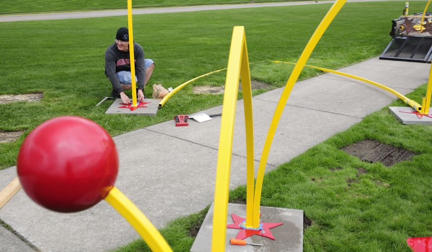Todd Kime, of Toledo, Ohio, installs a permanent version of his sculpture 'Bounce' along the Thomas Edison Parkway on May 15, 2015 in Port Huron, Mich. The sculpture will be a permanent piece of art in Port Huron. It was purchased, and then donated to the city. (Nicole Hayden/The Port Huron Times Herald via AP)  NO SALES