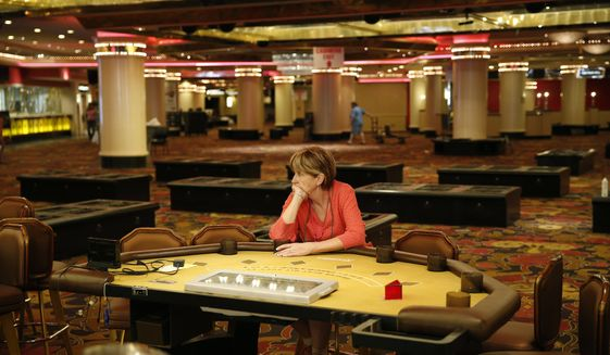 A woman who declined to give her name, sits at a table in the casino during a liquidation sale at the closed Riviera Hotel and Casino Thursday, May 14, 2015, in Las Vegas. The Riviera Hotel and Casino closed May 4, but everything inside the 2,075-room hotel-casino must go. National Content Liquidators has started selling it all at a public sale that started 9 a.m. Thursday.  (AP Photo/John Locher)