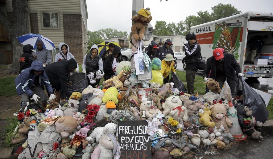 Volunteers remove items left at a makeshift memorial for Michael Brown Wednesday, May 20, 2015, in Ferguson, Mo. The memorial that has marked the place where Brown was fatally shot by a police officer in August has been removed and will be replaced with a permanent plaque, Ferguson's Mayor James Knowles said Wednesday. (AP Photo/Jeff Roberson)