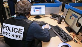 FILE- In this Jan. 19, 2015 file photo, a French police officer works at the headquarters of the Pharos reporting platform against cyber criminality, in Nanterre, outside Paris. Fearful of an expanding extremist threat, countries that for years have relied heavily on U.S. intelligence are quickly building up their own capabilities with new technology, new laws and _ in at least one case _ a searing debate on how much the American government should be allowed to spy on their own citizens. (AP Photo/Patrick Kovarik, pool, File)