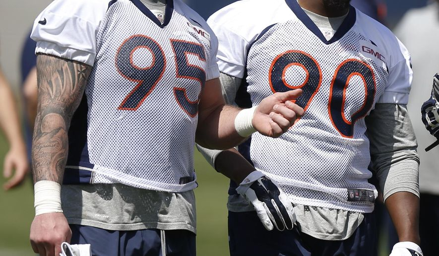 """FILE - In this April 28, 2015, file photo, Denver Broncos defensive ends Derek Wolfe, left, and Antonio Smith chat as they leave the field after the NFL football team's voluntary veterans minicamp in Englewood, Colo. Smith is under investigation in Texas over criminal allegations the local sheriff described as """"sexual in nature."""" Smith has not been arrested and no charges have been filed. (AP Photo/David Zalubowski, File)"""