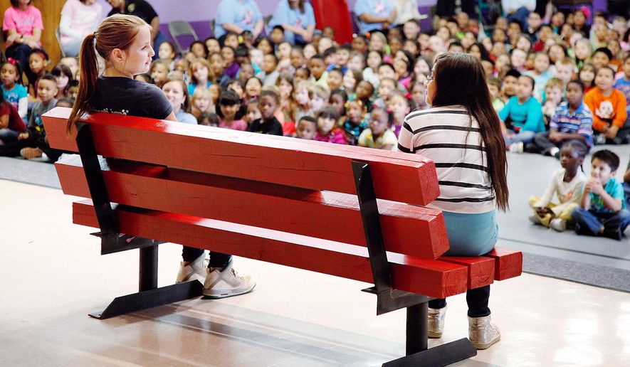 ADVANCED FOR RELEASE TUESDAY, MAY 26, 2015 Madison Ayscue, left, and Cristesbey Picaz simulate how the new Buddy Bench is to be used by students at the school. (Mark Dolejs/The Daily Dispatch via AP)