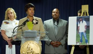 """D.C. Mayor Muriel Bowser (center), flanked by Police Chief Cathy Lanier (left) and ATF Special Agent in Charge Charlie Smith, pledged that investigators would find the person responsible for this """"act of evil."""" Daron Dylon Wint, 34, was named as the prime suspect in the May 14 quadruple homicide. (Associated Press)"""
