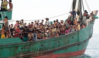 Migrants sit on their boat as they wait to be rescued by Acehnese fishermen on the sea off East Aceh, Indonesia, Wednesday, May 20, 2015. Hundreds of migrants stranded at sea for months were rescued and taken to Indonesia, officials said Wednesday, the latest in a stream of Rohingya and Bangladeshi migrants to reach shore in a growing crisis confronting Southeast Asia. (AP Photo/S. Yulinnas)