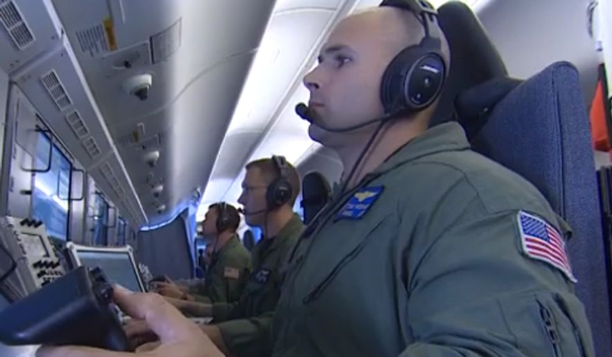A U.S. airman aboard a P8-A Poseidon surveillance aircraft monitors China's construction of artificial islands in the disputed South China Sea. (Image: CNN screenshot) ** FILE **