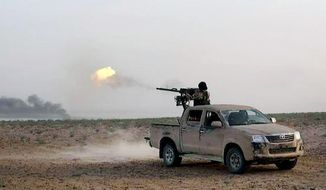 In this picture released on Wednesday, May 20, 2015, by the website of Islamic State militants, an Islamic State fighter fires his weapon during a battle against Syrian government forces on a road between Homs and Palmyra, Syria. Islamic State militants overran the famed archaeological site at Palmyra early on Thursday, just hours after seizing the central Syrian town, activists and officials said, raising concerns the extremists might destroy some of the priceless ruins as they have done in neighboring Iraq. (The website of Islamic State militants via AP)