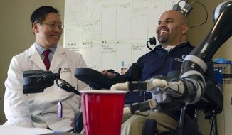 In this April 14, 2015, file photo provided by the California Institute of Technology, Dr. Charles Y. Liu, left, a neurosurgeon at the University of Southern California, laughs with patient Erik Sorto in Pasadena, Calif. Liu led a team of doctors that implanted tiny chips into Sorto's brain in 2013 to allow him to control a robotic arm using his thoughts. It's the latest attempt at creating mind-controlled prosthetics to help disabled people gain more independence. (Lance Hayashida/Caltech via AP) ** FILE **