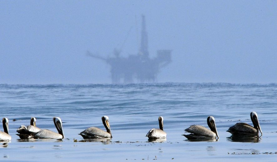 FILE - This May 13, 2010 file photo Pelicans float on the water as an oil platform sits in the background off the coast of Santa Barbara, Calif.    More than 7,700 gallons of oil has been raked, skimmed and vacuumed from a spill that stretched across 9 miles of California coast, just a fraction of the sticky, stinking goo that escaped from a broken pipeline, officials said on Thursday, May 21, 2015.  (AP Photo/Mark J. Terrill,File)