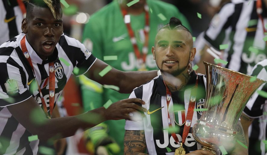 Juventus' Arturo Vidal, right, and teammate Paul Pogba celebrate with the trophy at the end of the Italian Cup soccer final match between Lazio and Juventus at Rome's Olympic stadium, Wednesday, May 20, 2015. Juventus won 2 - 1. (AP Photo/Gregorio Borgia)