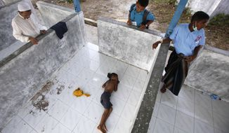 A Rohingya boy sleeps on the floor at a temporary shelter in Langsa, Aceh province, Indonesia, Thursday, May 21, 2015. (AP Photo/Binsar Bakkara)