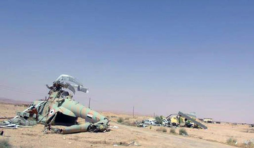 This picture released on Thursday, May 21, 2015 by the website of Islamic State militants, shows damaged Syrian military helicopters at Palmyra air base that was captured by the Islamic State militants after a battle with the Syrian government forces in Palmyra, Syria. Activist and officials say members of the Islamic State group are conducting search operations in the ancient town of Palmyra where they have detained and killed dozens of people. (The website of Islamic State militants via AP)