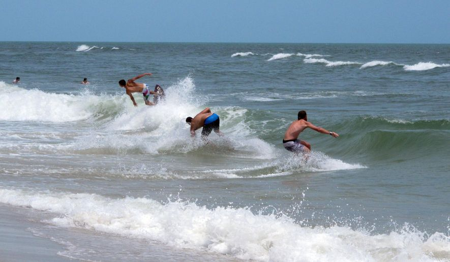 This June 30, 2014 photo,  surfers ride waves in Ship Bottom, N.J. on Long Beach Island. Two New Jersey lawmakers on Friday May 22, 2015 called on Rutgers University to cancel planned ocean blasting tests off Long Beach island that they say will harm marine life and threaten new Jersey's crucial tourism industry. (AP Photo/Wayne Parry)