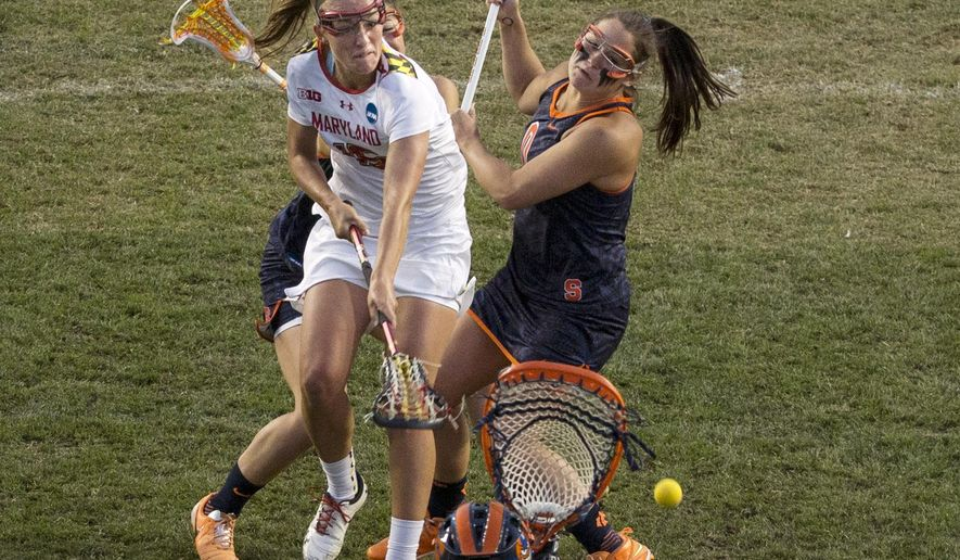 Maryland's midfielder Zoe Stukenberg, center, splits the Syracuse defense as she shoots on Syracuse's goalie Kelsey Richardson, bottom, during the first half of the semifinals in the NCAA Division I women's college lacrosse tournament, Friday, May 22, 2015, in Chester, Pa. (AP Photo/Chris Szagola)