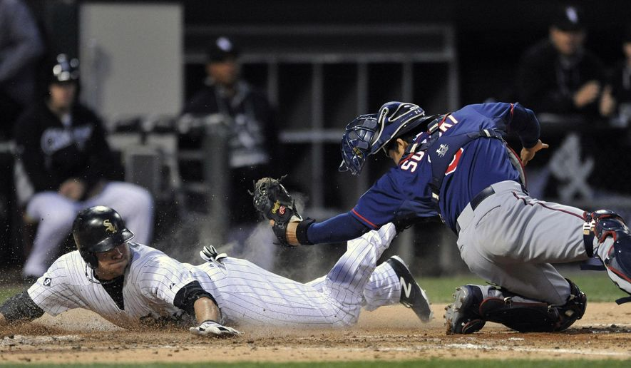 Chicago White Sox's J.B. Shuck (20), slides into home plate safely as Minnesota Twins catcher Kurt Suzuki (8), tries to apply the tag after Chicago White Sox's Geovany Soto hit a 2 RBI double during the fourth inning of a baseball game in Chicago, Friday, May 22, 2015. (AP Photo/Paul Beaty)