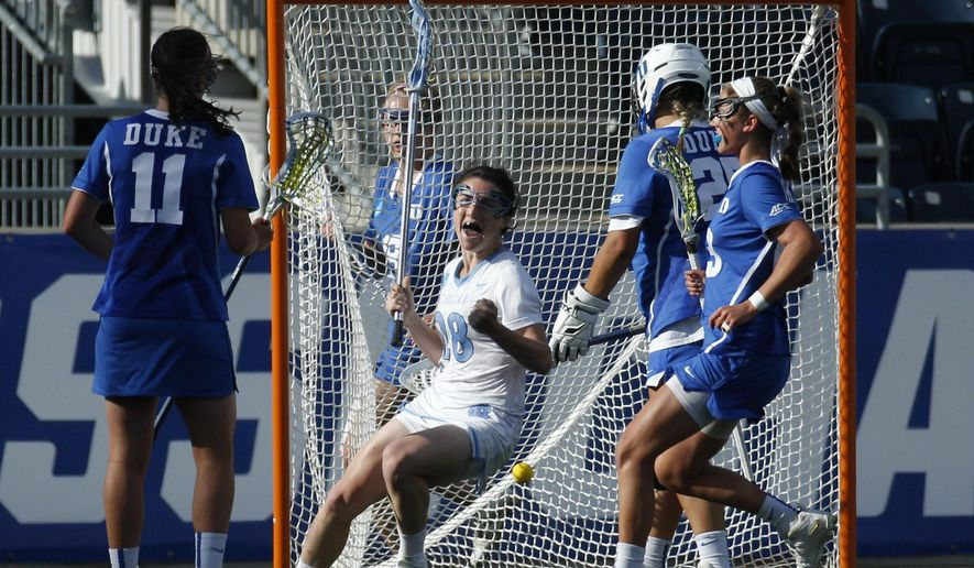 North Carolina's defender Courtney Waite, center, reacts to her goal on Duke's goalie Kelsey Duryea, center right, during the first half of the semifinals in the NCAA Division I women's lacrosse tournament, Friday, May 22, 2015, in Chester, Pa. (AP Photo/Chris Szagola)
