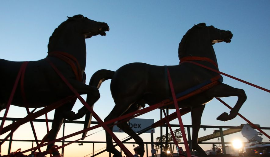 Two bronze horse statues by artist Josef Thorak are transported on a flatbed trailer in Bad Duerkheim, southwestern Germany, Thursday, May 21, 2015. A German investigation into black market art had recovered the two statues that once stood in front of Adolf Hitler's grand chancellery building in Berlin as well as other Nazi-era pieces that had been lost for decades. Police in five states conducted coordinated raids during more than a yearlong investigation into illegal art trafficking. (Fredrik von Erichsen/dpa via AP)