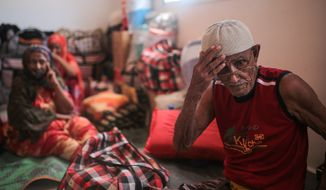 In this Tuesday, May 19, 2015, photo, Ibrahim Mohamed, 80, and the oldest refugee at the center, who is both blind and deaf, adjusts his hat, at an orphanage that has been turned into a center for Yemeni refugees, in Obock, northern Djibouti. (AP Photo/Mosa'ab Elshamy)