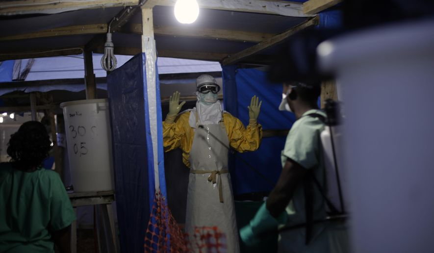 FILE - In this Thursday Nov. 20, 2014 file photo, an MSF Ebola heath worker is sprayed as he leaves the contaminated zone at the Ebola treatment centre in Gueckedou, Guinea. Authorities in the country where the Ebola epidemic began are concerned about a new outbreak of cases just as officials hoped the crisis was coming under control. (AP Photo/Jerome Delay, File)