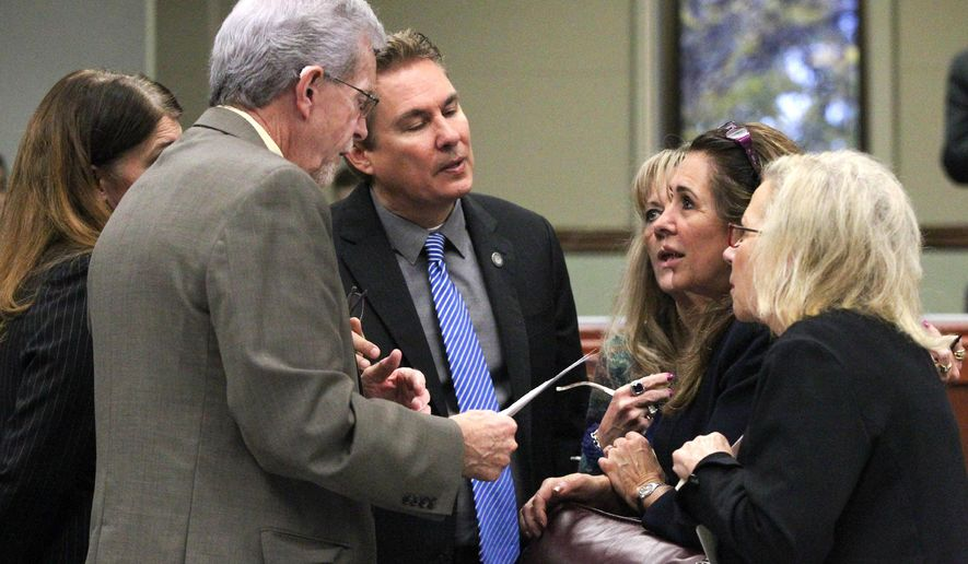 Nevada Assembly Republicans, from left, Shelly Shelton, Glenn Trowbridge, Brent Jones, Jill Dickman, Victoria Seaman and Victoria Dooling talk on the Assembly floor at the Legislative Building in Carson City, Nev., on Friday, May 22, 2015. Lawmakers work Friday to vote dozens of bills out of the Senate and Assembly as they face down a major deadline. (AP Photo/Cathleen Allison)