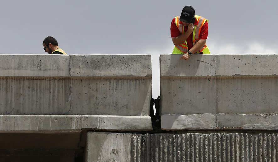 Workers inspect damage to a freeway ramp Friday, May 22, 2015, in Las Vegas. The ramp leading to Interstate 15 was closed from damage after an earthquake that struck a rural area of southern Nevada. (AP Photo/John Locher)