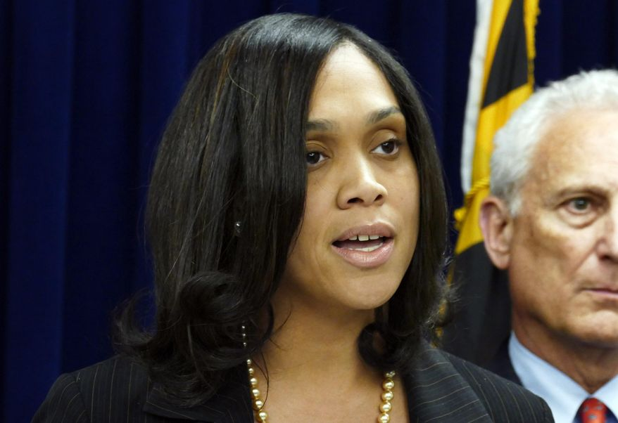 """Baltimore States Attorney Marilyn Mosby, center, announces the indictments of six Baltimore Police officers Thursday, May 21, 2015, on various charges related to the arrest and death of Freddie Gray. The indictments were very similar to the charges Mosby announced about three weeks ago. The most serious charge for each officer, ranging from second-degree """"depraved heart"""" murder to assault, still stood. (Kevin Richardson/The Baltimore Sun via AP)"""