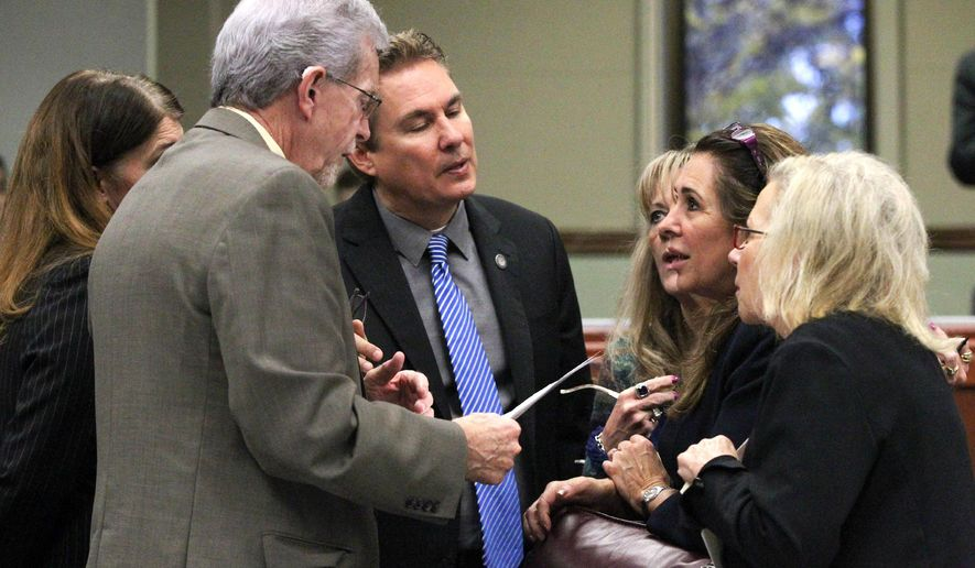FILE - In this May 22, 2015 file photo, Nevada Assembly Republicans, from left, Shelly Shelton, Glenn Trowbridge, Brent Jones, Jill Dickman, Victoria Seaman and Victoria Dooling talk on the Assembly floor at the Legislative Building in Carson City, Nev. A hard-fought bill to regulate ride-hailing companies such as Uber and Lyft got the green light from Nevada lawmakers in the wee hours of Saturday morning, May 23, 2015, after weeks of behind-the-scenes negotiations, several public failures for Uber and a marathon workday that ended with legislators apparently confused over which bills they were voting on. (AP Photo/Cathleen Allison, File)