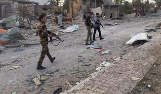 In this April 23, 2015, file photo, Iraqi security forces and tribal fighters regain control of the northern neighborhoods, after overnight heavy clashes with Islamic State group militants, in Ramadi, 70 miles (115 kilometers) west of Baghdad, Iraq. (Associated Press) **FILE**