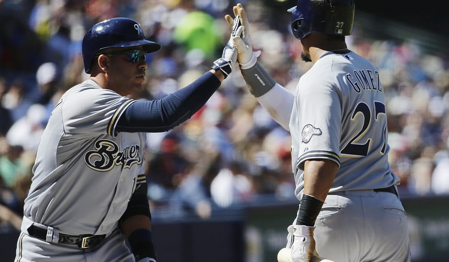 Milwaukee Brewers' Carlos Gomez, right, is high-fived by teammate Aramis Ramirez after scoring off a single by Ryan Braun in the first inning of a baseball game against the Atlanta Braves Saturday, May 23, 2015, in Atlanta. (AP Photo/David Goldman)
