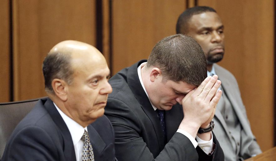 Michael Brelo, center, listens to the judge reading his verdict during his trial Saturday, May 23, 2015, in Cleveland. (AP Photo/Tony Dejak)