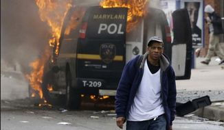 A police van burns in Baltimore, April 27, 2015, during riots sparked by the death of Freddie Gray. Mr. Gray, 25, died April 19 after being taken into custody by Baltimore cops April 12. (Associated Press) ** FILE **