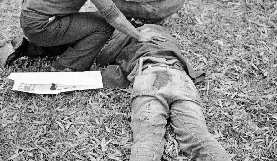 """FILE - In this Nov. 3, 1979 file photo, Workers Viewpoint Organization member Nelson Johnson kneels by victim in aftermath of shooting in Greensboro, N.C.  The state, with the blessing of the Greensboro City Council, will use the word """"massacre"""" for a highway historical marker commemorating the deaths of five Communist Workers Party members during a confrontation with Ku Klux Klansmen and the American Nazi Party. The marker, which will be dedicated Sunday, May 24, 2015.  (Jim Stratford /News & Record via AP)"""