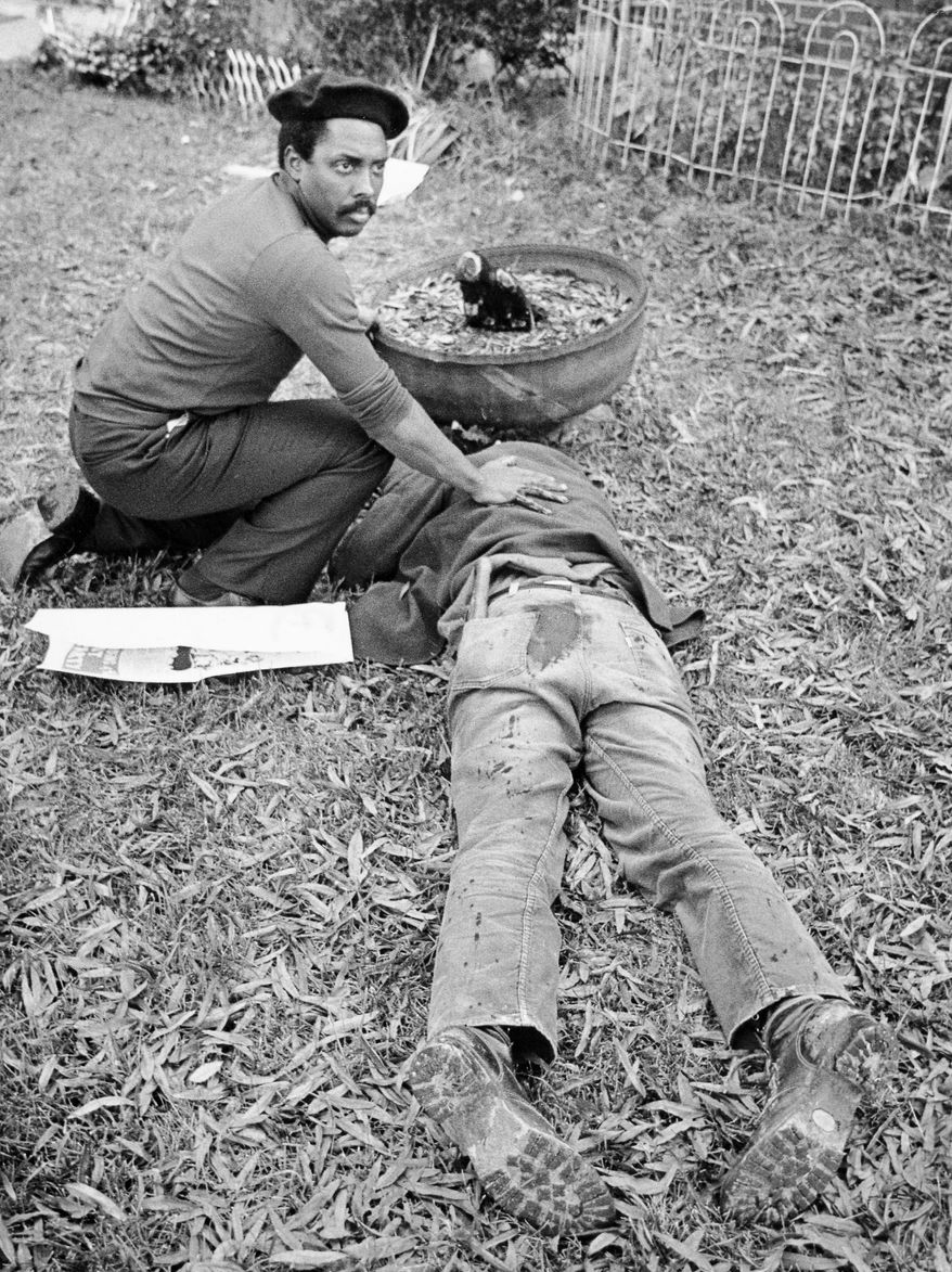 "FILE - In this Nov. 3, 1979 file photo, Workers Viewpoint Organization member Nelson Johnson kneels by victim in aftermath of shooting in Greensboro, N.C.  The state, with the blessing of the Greensboro City Council, will use the word ""massacre"" for a highway historical marker commemorating the deaths of five Communist Workers Party members during a confrontation with Ku Klux Klansmen and the American Nazi Party. The marker, which will be dedicated Sunday, May 24, 2015.  (Jim Stratford /News & Record via AP)"