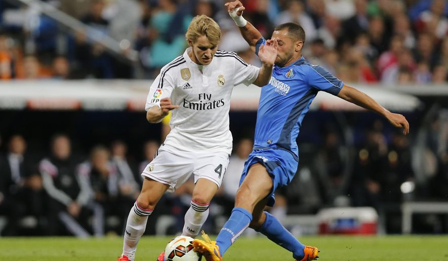 Real Madrid's Martin Odegaard from Norway, left, duels for the ball with Getafe's Lacen, right, during a Spanish La Liga soccer match between Real Madrid and Getafe at the Santiago Bernabeu stadium in Madrid, Spain, Saturday, May 23, 2015. (AP Photo/Daniel Ochoa de Olza)