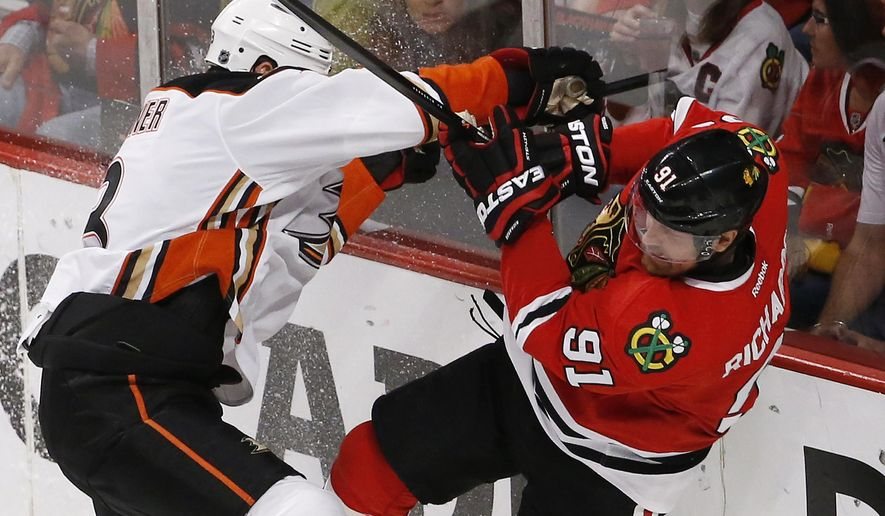 Anaheim Ducks defenseman Clayton Stoner, left, checks Chicago Blackhawks center Brad Richards (91) during the second period in Game 4 of the Western Conference finals of the NHL hockey Stanley Cup playoffs, Saturday, May 23, 2015, in Chicago. (AP Photo/Charles Rex Arbogast)