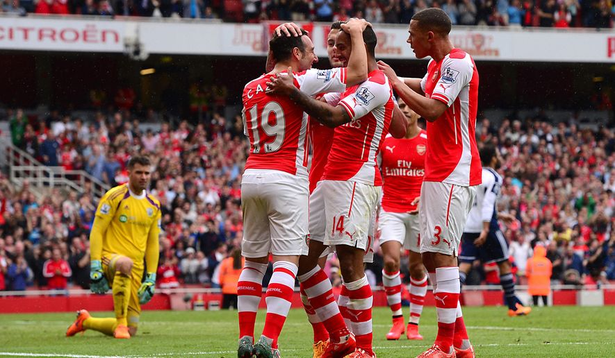 Arsenal's Theo Walcott, center, celebrates scoring his side's fourth goal against West Bromwich Albion with teammates during the English Premier League soccer match at the Emirates Stadium, London, Sunday May 24, 2015. (Dominic Lipinski/PA via AP) UNITED KINGDOM OUT  NO SALES  NO ARCHIVE