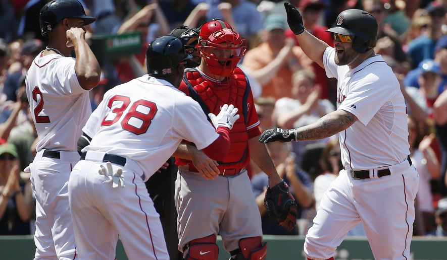 Boston Red Sox's Mike Napoli, right, celebrates his two-run home run with teammates Rusney Castillo (38) and Xander Bogaerts (2) as Los Angeles Angels' Chris Iannetta, center, looks on during the second inning of a baseball game in Boston, Sunday, May 24, 2015. (AP Photo/Michael Dwyer)