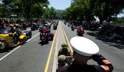 Looking ahead: Marine Tim Chamber and Army veteran Eric Cantu saluted during the Rolling Thunder Ride for Freedom on Sunday. Although the event has grown, the number of riders who fought in Vietnam is dwindling. (Associated Press)