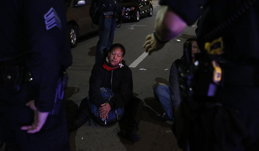 In this May 23, 2015 photo, Cat Brooks listens to Oakland police officers as they tell her she is to be arrested for refusing to disperse in Oakland, Calif. About 100 people took to the streets in Oakland on Saturday night to protest against what they said was the city's crackdown on nighttime demonstrations. (Leah Millis/San Francisco Chronicle via AP)  MANDATORY CREDIT PHOTOG & CHRONICLE; MAGS OUT; NO SALES