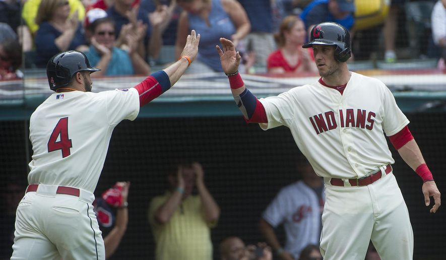 Cleveland Indians' Mike Aviles is greeted Yan Gomes after Aviles scoring against the Cincinnati Reds during the sixth inning of a baseball game against the Cleveland Indians, in Cleveland, Sunday, May 24, 2015. (AP Photo/Phil Long)