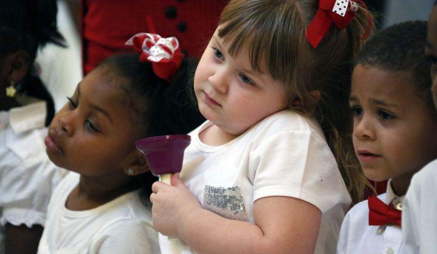 Angel Nevins, center and her friend and classmate Jade Smith, left, wait for their signal to ring their hand bell as children from the Anderson Grove Head Start program in Caledonia, Miss., ring their hand bells to accompany several patriotic songs, Tuesday, Feb. 26, 2013 at the Capitol in Jackson, Miss., at the conclusion of a rally by early childhood education supporters, childcare providers and supporters who called for support of the Mississippi Pre K Collaborative Act before this year's legislature. The groups lobbied their lawmakers to support the legislation that provides funding for local partnerships between public, parochial and private schools and licensed child care programs in some parts of the state.  (AP Photo/Rogelio V. Solis)