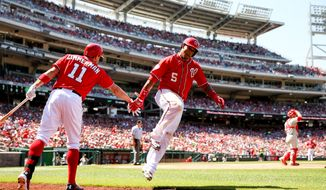 Washington Nationals' Ryan Zimmerman, left, celebrates with Washington Nationals' Yunel Escobar as he scores on a RBI hit by Washington Nationals' Bryce Harper in the fifth inning during a baseball game against the Philadelphia Phillies, Sunday, May 24, 2015, at Nationals Park in Washington. (AP Photo/Andrew Harnik)