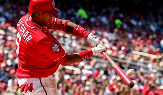 Washington Nationals' Yunel Escobar hits a triple into deep right center field in the fifth inning during a baseball game against the Philadelphia Phillies, Sunday, May 24, 2015, in Washington. (AP Photo/Andrew Harnik)
