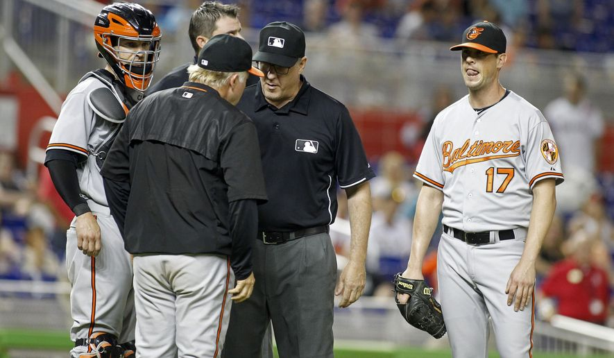 Baltimore Orioles relief pitcher Brian Matusz (17) waits as umpire Paul Emmel, center, speaks with Orioles manager Buck Showalter, as catcher Caleb Joseph stands nearby during the 12th inning of a baseball game in Miami, Saturday, May 23, 2015. Matusz left the game after his forearm was inspected. The Marlins won 1-0. (AP Photo/Joe Skipper)