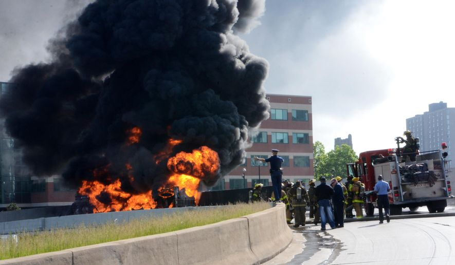 Police and firefighters watch a tanker truck that was carrying 9,000 gallons of unleaded fuel burn after it exploded and caught fire on Interstate 75 in downtown Detroit Sunday, May 24, 2015. The driver wasn't hurt, but Interstate 375 at I-75 remained shut down as well as north I-75 in the area. (AP Photo/Bill Eisner)