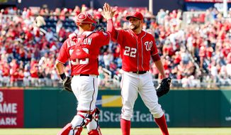 Washington Nationals' catcher Jose Lobaton, left, and relief pitcher Drew Storen celebrate following a baseball game against the Philadelphia Phillies, Sunday, May 24, 2015, in Washington. The Nationals won 4-1. (AP Photo/Andrew Harnik)