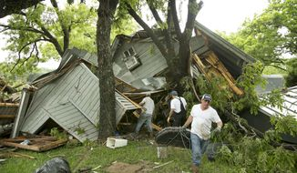 Jeremy Steele, left, Ric Jaime, center, and Keith McNabb salvage belongings at their friend Mike Cook's house near Wimberley, Texas, Sunday, May 24, 2015. (Jay Janner/Austin American-Statesman via AP)