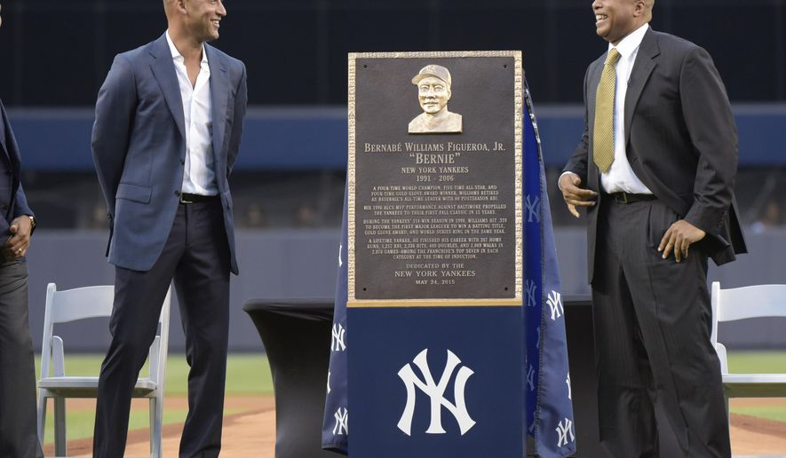 Former New York Yankees Bernie Williams, right, and Derek Jeter react as they stand by a replica of Williams' plaque, which will be displayed in Monument Park, before a baseball game against the Texas Rangers Sunday, May 24, 2015, at Yankee Stadium in New York. (AP Photo/Bill Kostroun)