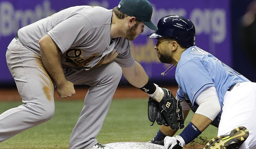 Tampa Bay Rays' James Loney, right, steals third base ahead of the tag by Oakland Athletics third baseman Max Muncy during the eighth inning of a baseball game Sunday, May 24, 2015, in St. Petersburg, Fla.  The A's won the game 7-2. (AP Photo/Chris O'Meara)
