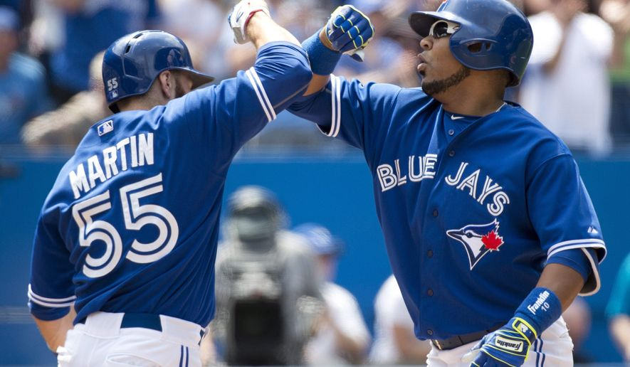 Toronto Blue Jays' Edwin Encarnacion, right, celebrates his two-run home run with teammate Russell Martin, left, against the Seattle Mariners during the fifth inning of a baseball game Sunday, May 24, 2015, in Toronto. (Nathan Denette/The Canadian Press via AP) MANDATORY CREDIT