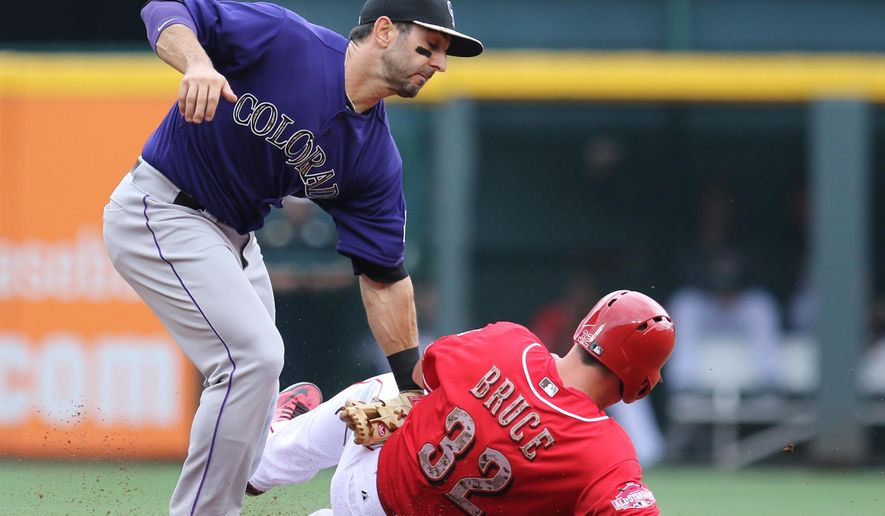Colorado Rockies' shortstop Daniel Descalso (3) tags out Cincinnati Reds' Jay Bruce (32) as Bruce attempts to steal second base during the first inning of their baseball game Monday, May 25, 2015, in Cincinnati. (AP Photo/Gary Landers)
